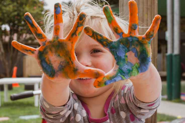 photo of little girl s hands covered with paint